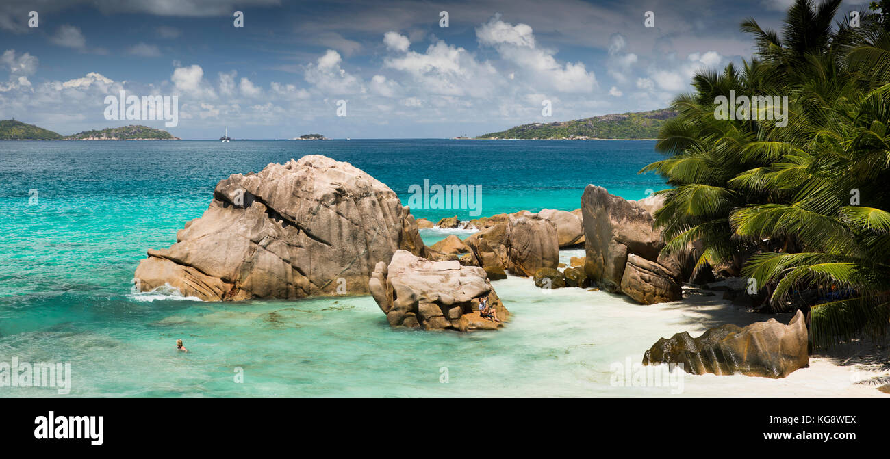 The Seychelles, La Digue, Anse Patates, tourist in sea sheltered behind huge granite rocks - Stock Image