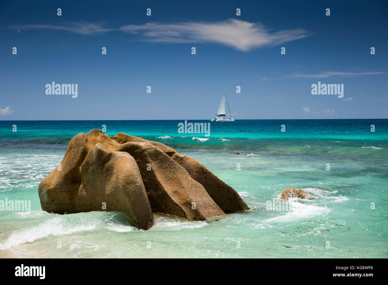The Seychelles, La Digue, Anse Grosse Roche, sailing catamaran passing huge granite rocks - Stock Image