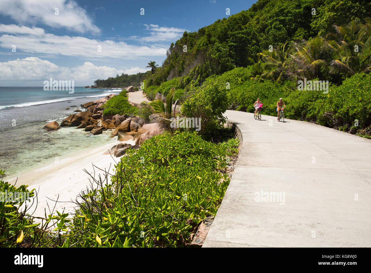 The Seychelles, La Digue, Anse Formis, two older tourists cycling on empty east coast road Stock Photo