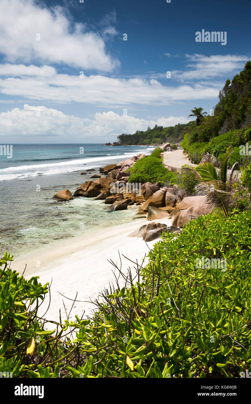 The Seychelles, La Digue, Anse Formis, empty east coast beach beside road Stock Photo