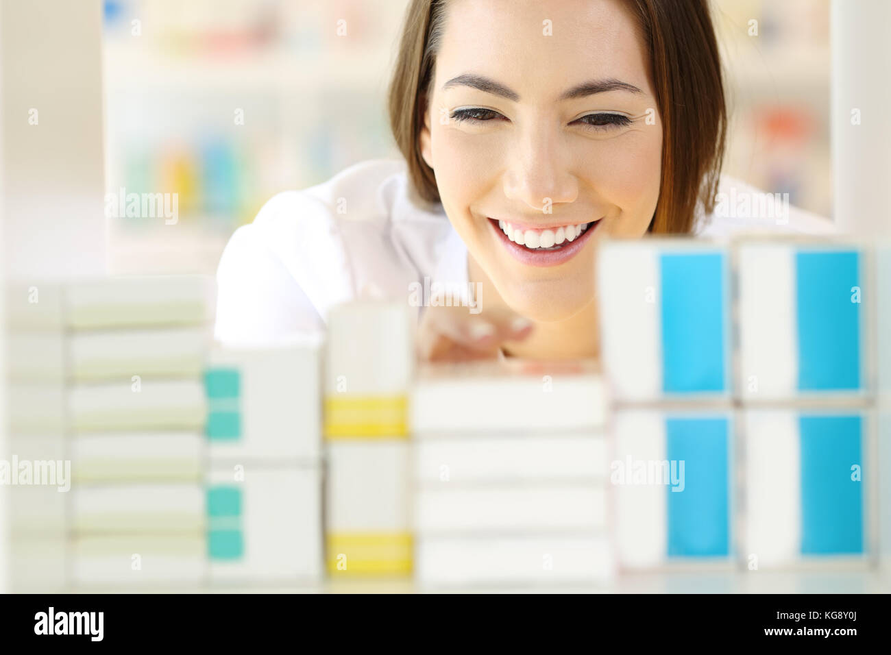 Front view portrait of a satisfied pharmacist searching medicines in a pharmacy shelf - Stock Image