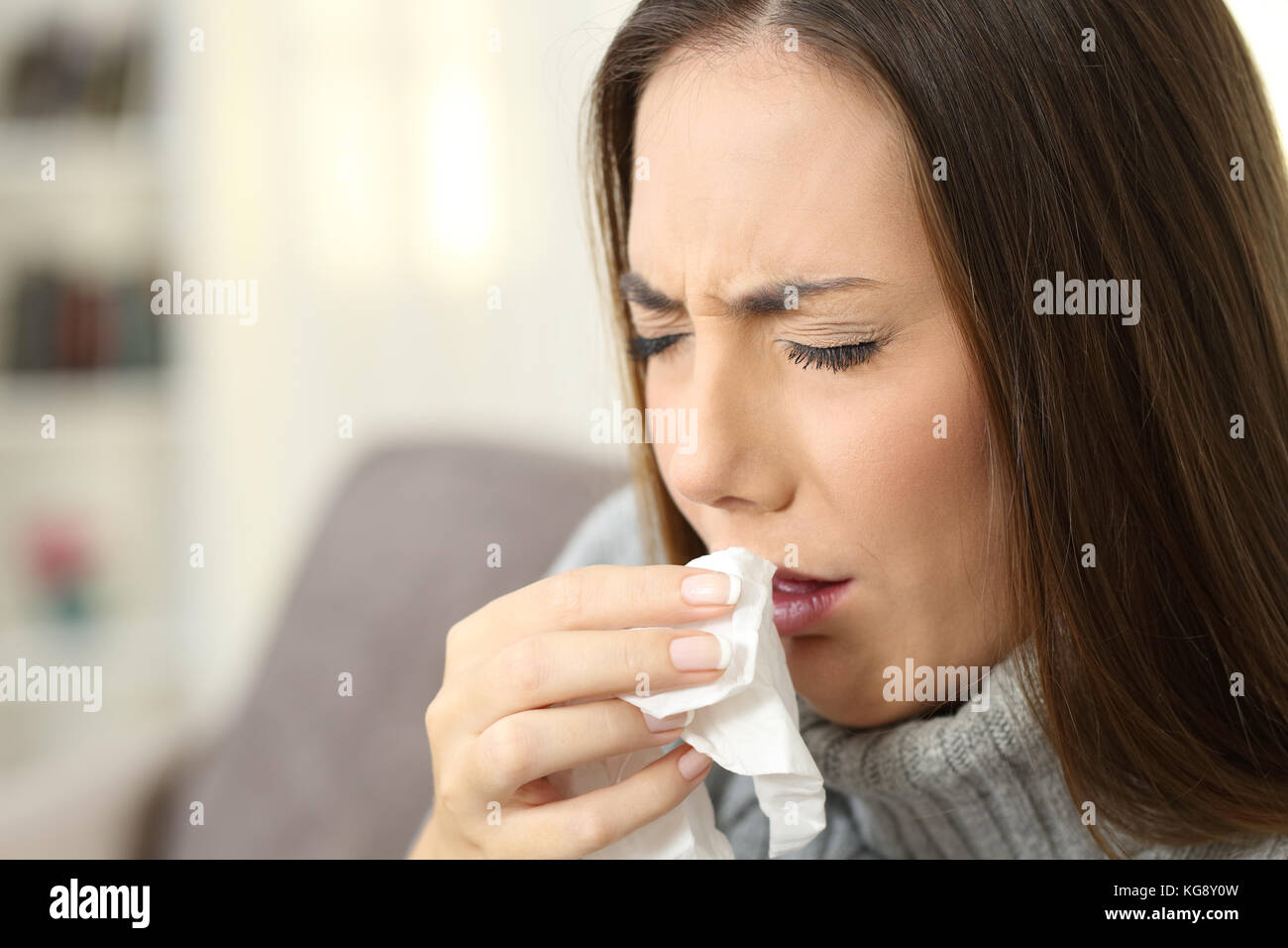 Ill woman coughing using a tissue sitting on a couch in the living room in a house interior - Stock Image