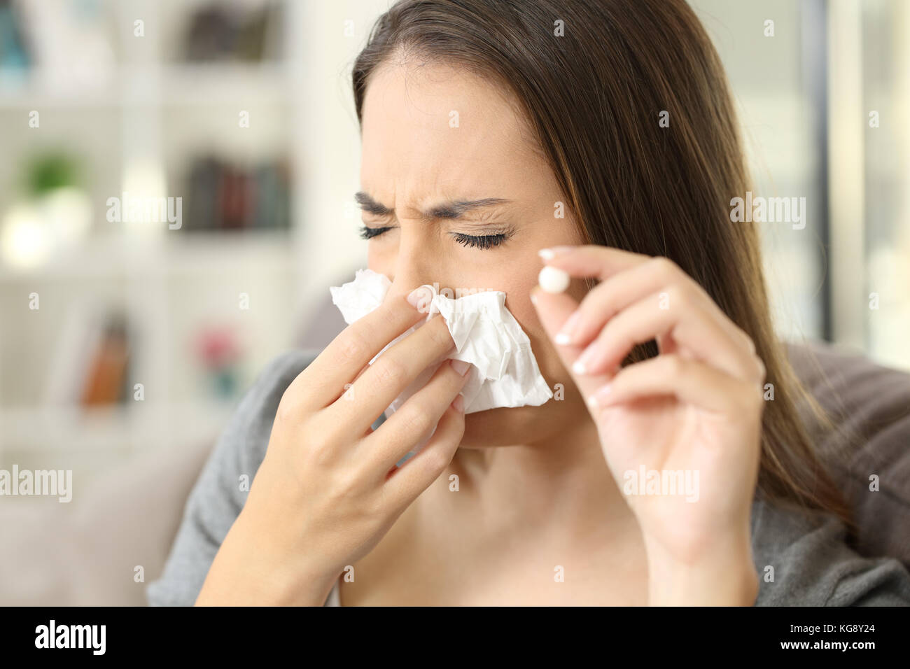 Woman coughing covering mouth with a tissue and holding a pill sitting on a sofa in a house interior - Stock Image