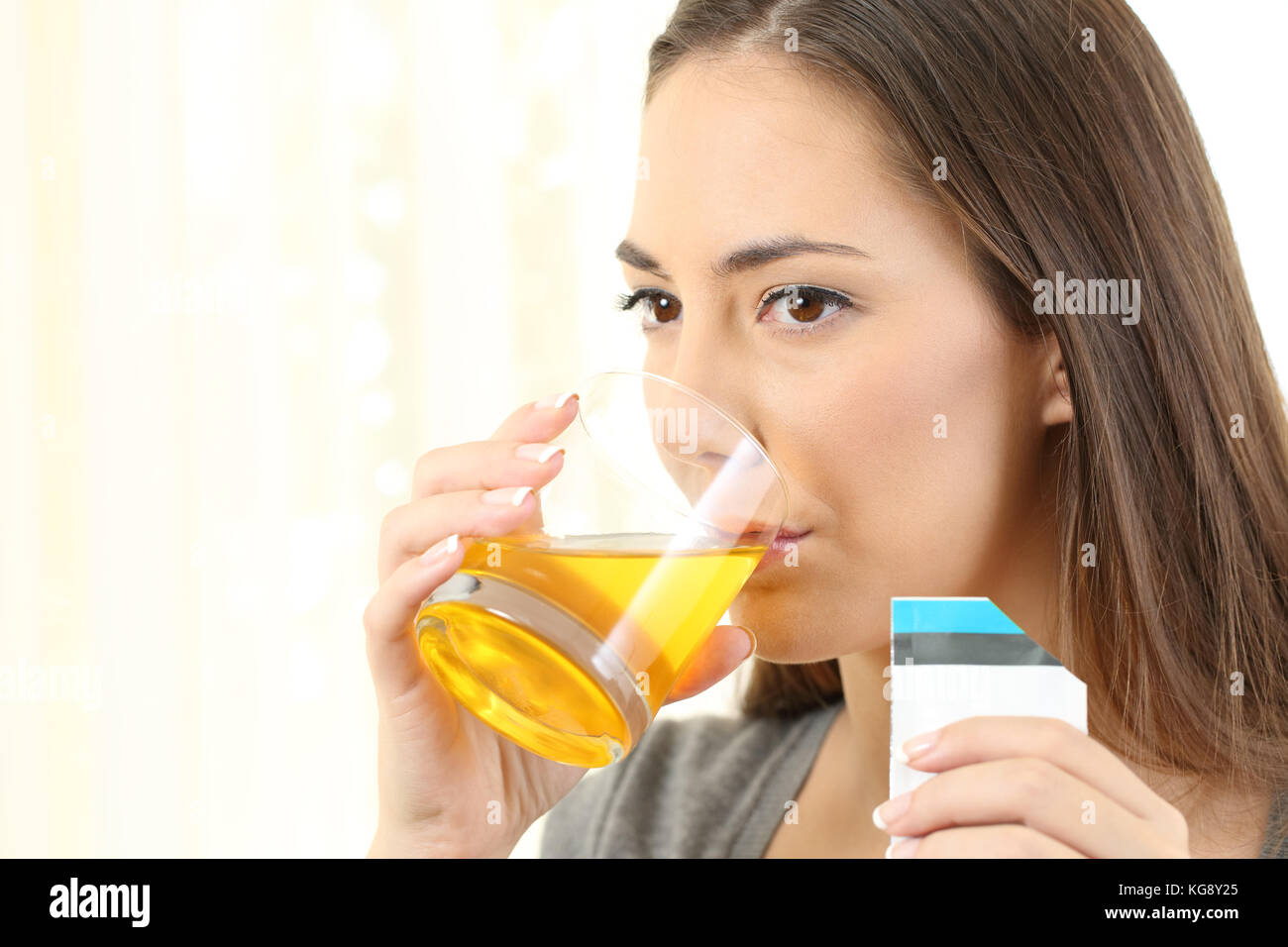 Serious woman drinking an orange liquid medicine in a house interior - Stock Image