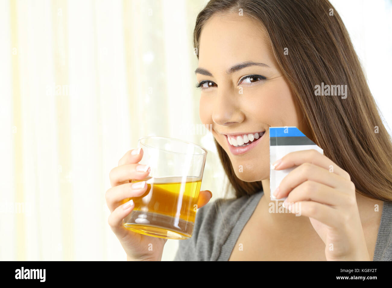 Happy woman posing holding a glass of soluble orange liquid medicine in a house interior - Stock Image
