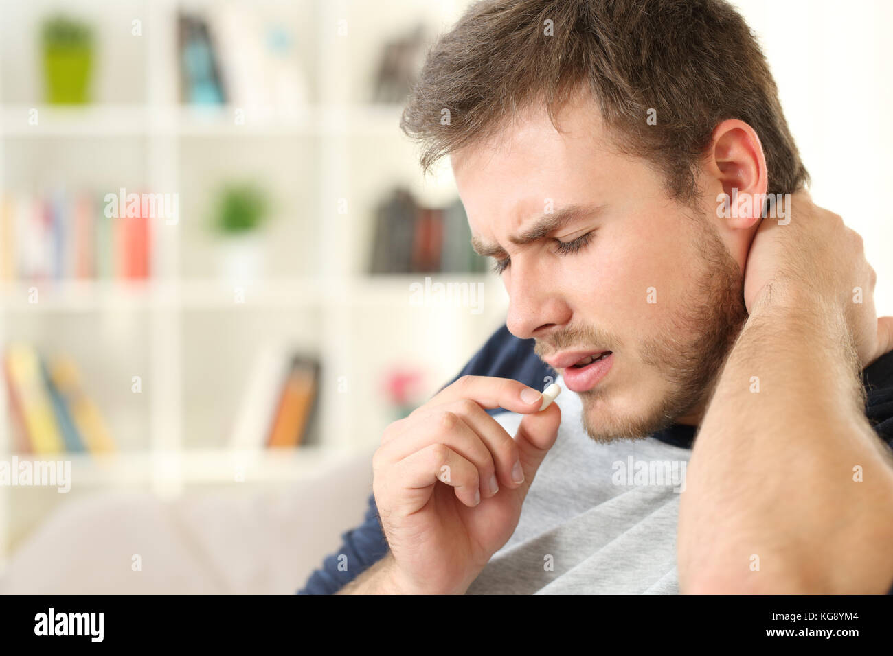Injured man complaining taking a pill sitting on a couch in the living room in a house interior - Stock Image