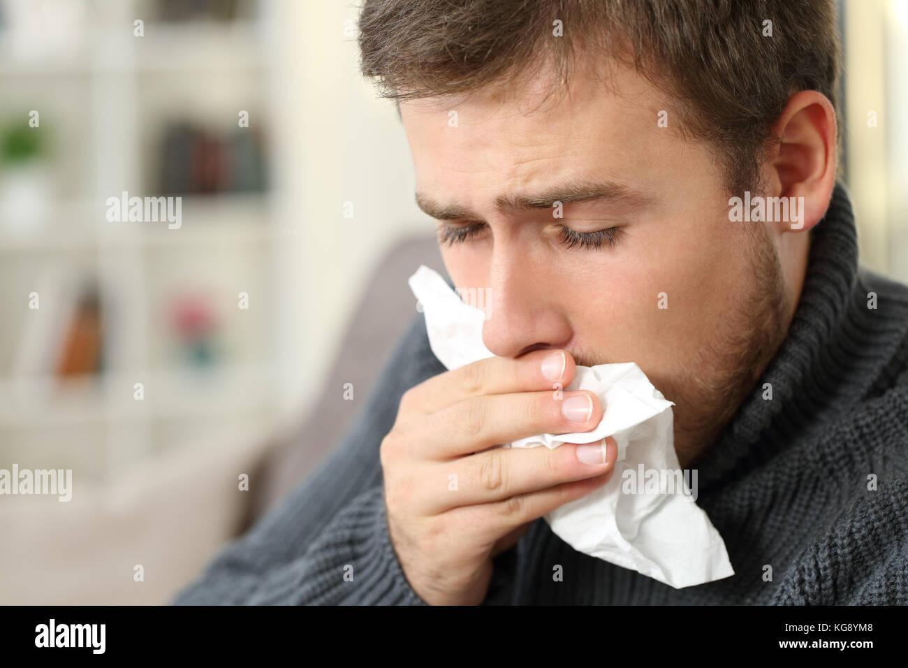 Man coughing covering mouth with a tissue sitting on a couch in a house interior - Stock Image