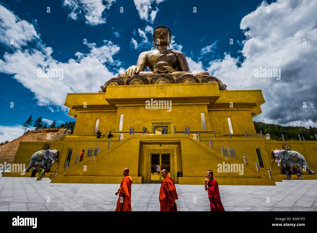 Monks walking by a giant Buddha statue in Bhutan - July 2017 - Stock Image