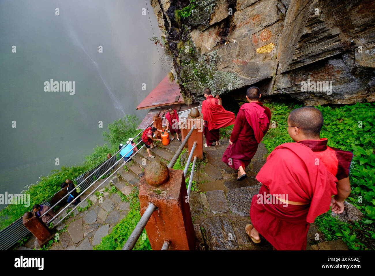 Monks walking the cliffs by Tiger's nest monastery in Bhutan - July 2017 - Stock Image
