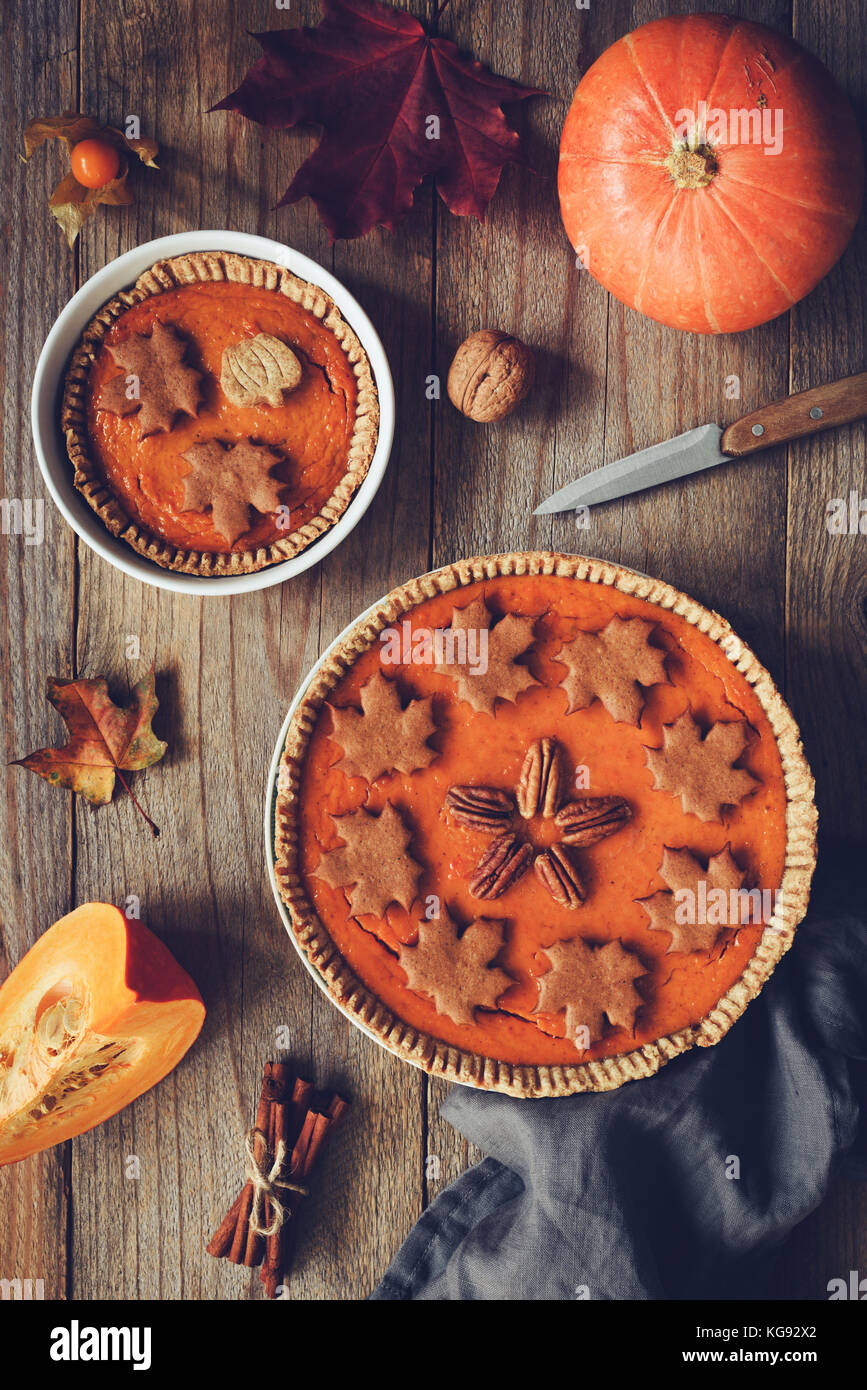 Homemade Pumpkin pie for Thanksgiving dinner on wooden table. Top view. Autumn food, Thanksgiving day food. Vertical, - Stock Image