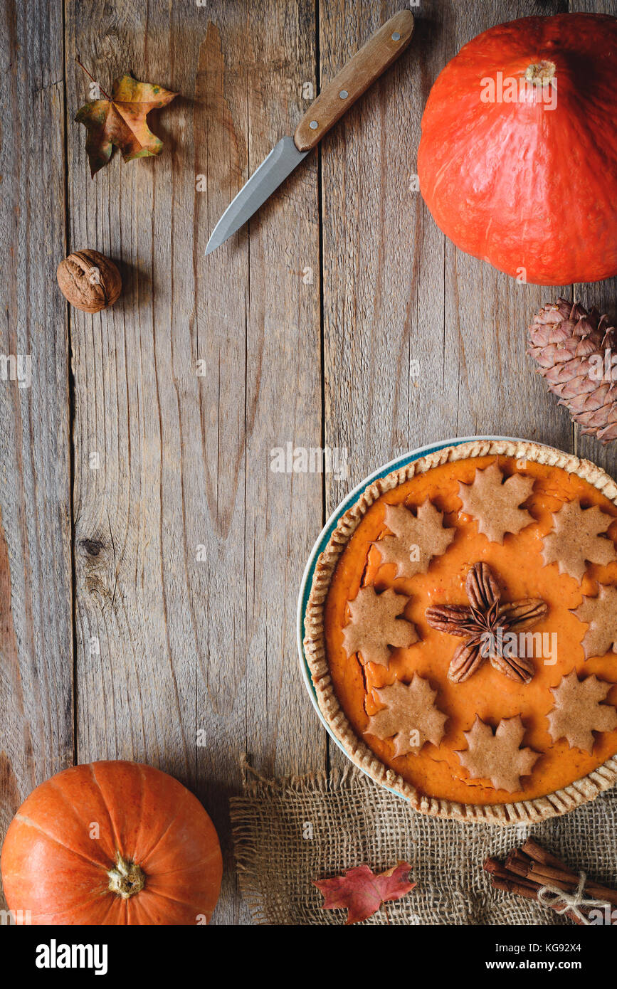 Pumpkin pie, pumpkins, knife and maple leaf on old wooden table. Copy space for text. Fall comfort food, Thanksgiving - Stock Image