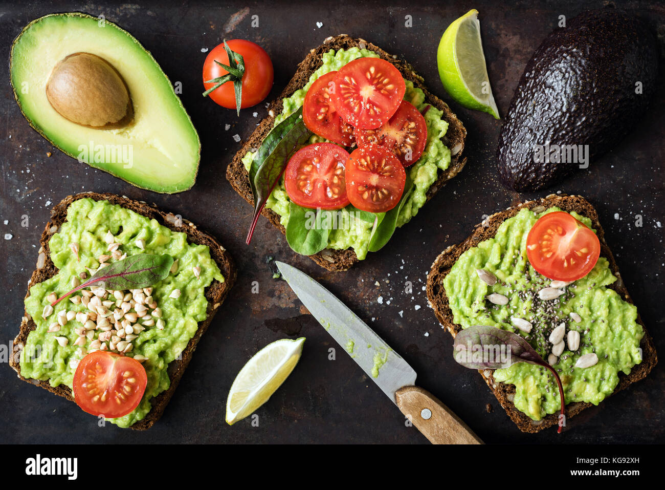 Healthy green veggie toast with avocado, tomato, sprouts and seeds on dark backgrop. Table top view. Healthy food, - Stock Image
