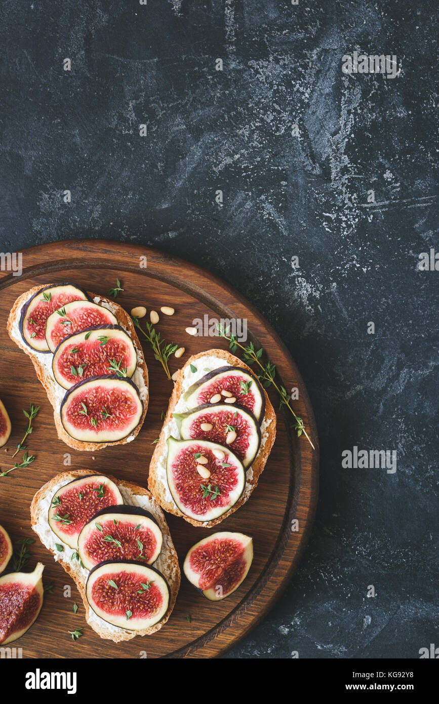 Fig and cheese appetizer toast or bruschetta on cutting board. Top view with copy space for text - Stock Image