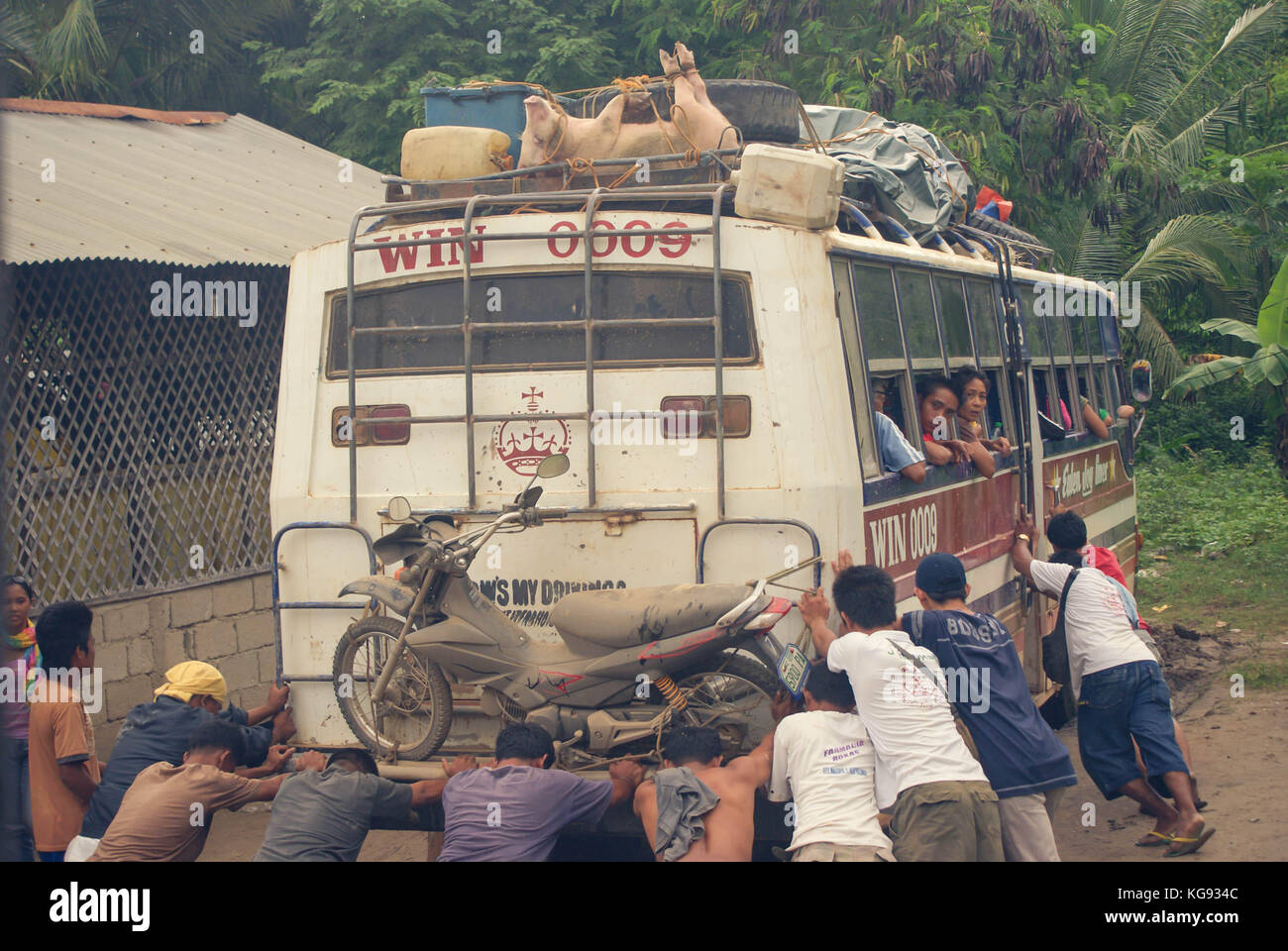Palawan, Philippines - May 17, 2009: Local people push the overloaded bus stuck in the muddy road. Journey from - Stock Image