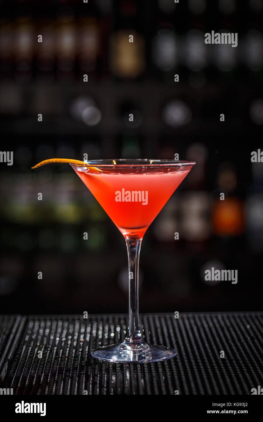 Closeup glass of cosmopolitan cocktail decorated with orange peel at bar background - Stock Image