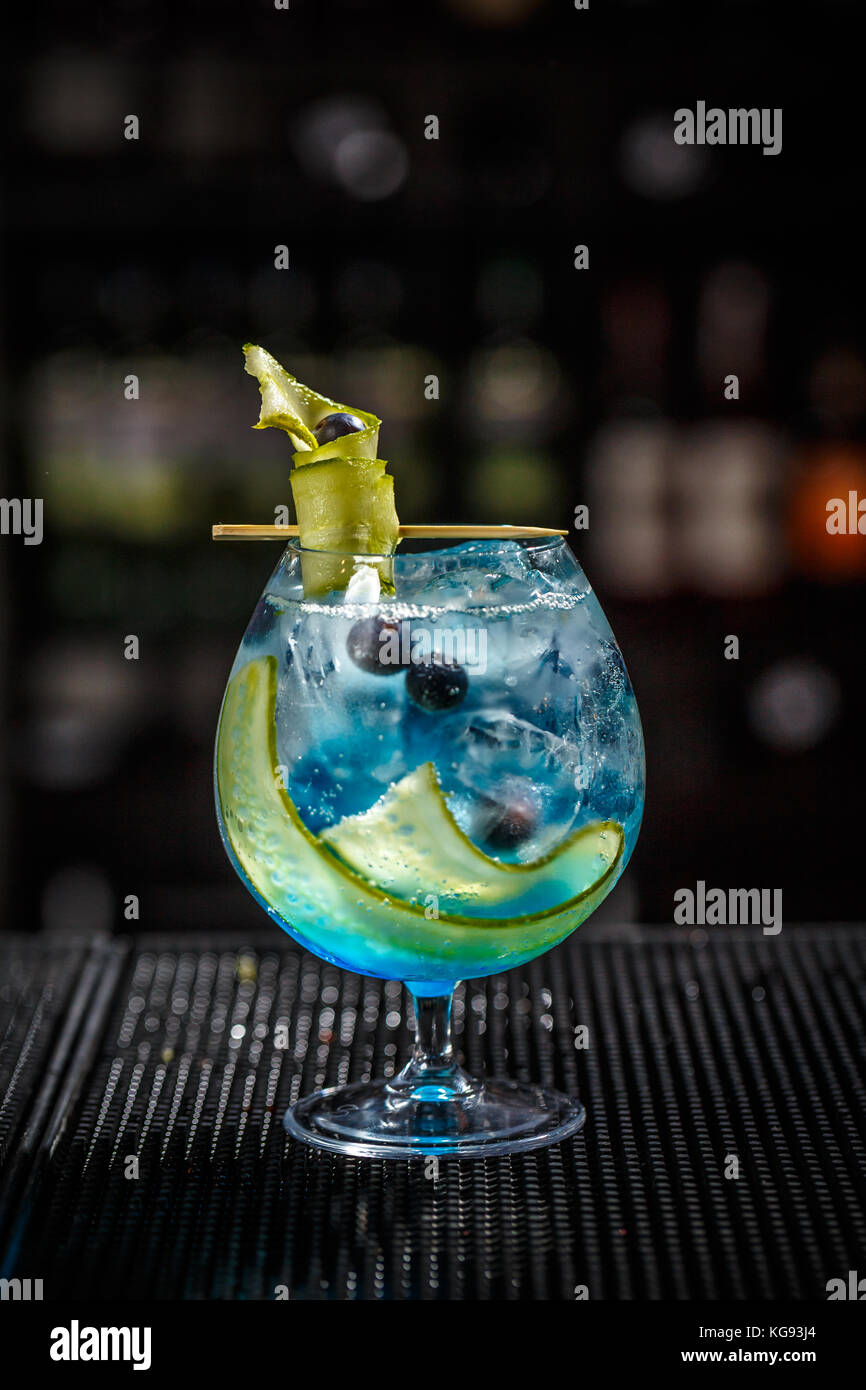 Blue gin tonic with cucumber served on the bar counter - Stock Image