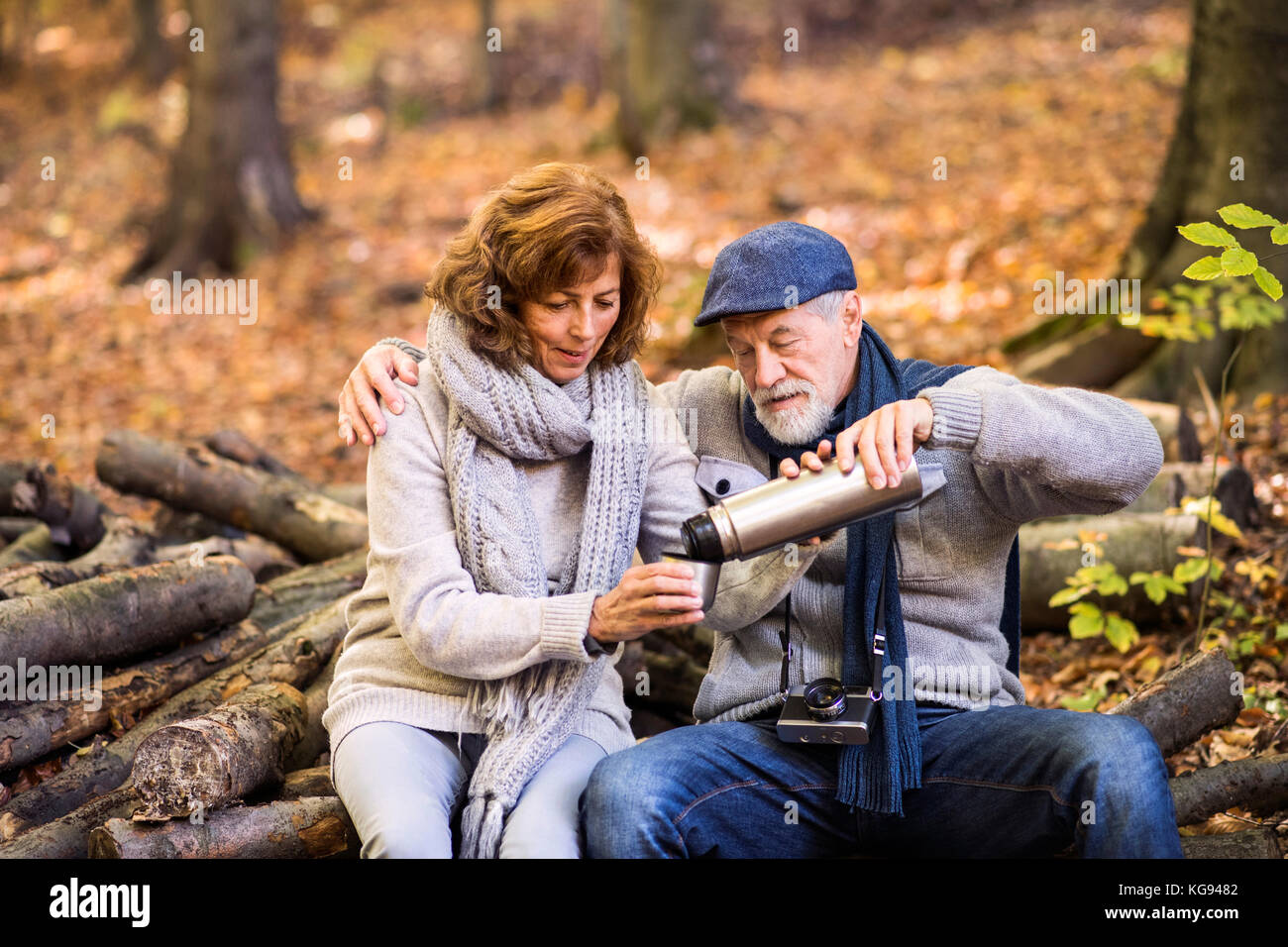 Senior couple on a walk in autumn forest. - Stock Image