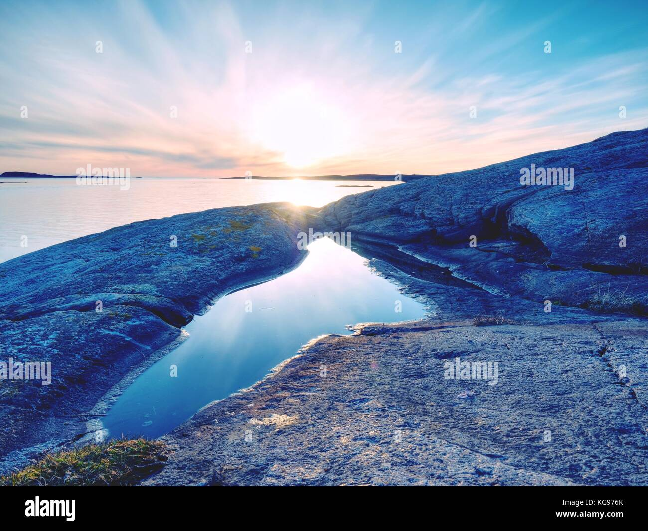 Beautiful seascape view. The mirroring of  sunsetting horizon in water pools in the rocks . Smooth ocean with light - Stock Image