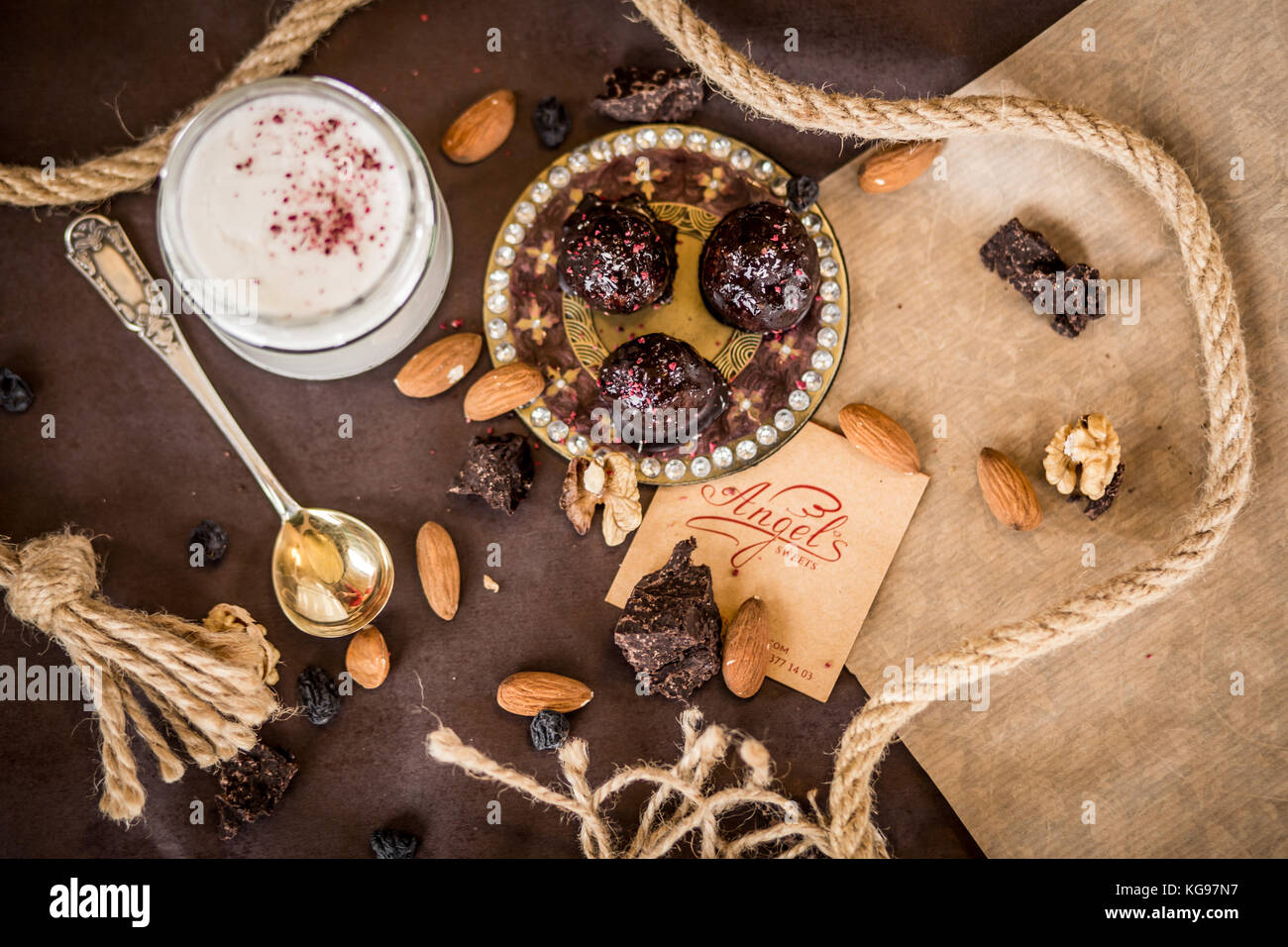 dessert composition coconut cream with strawberries and nuts on a brown background with a decorative lace and chocolate - Stock Image