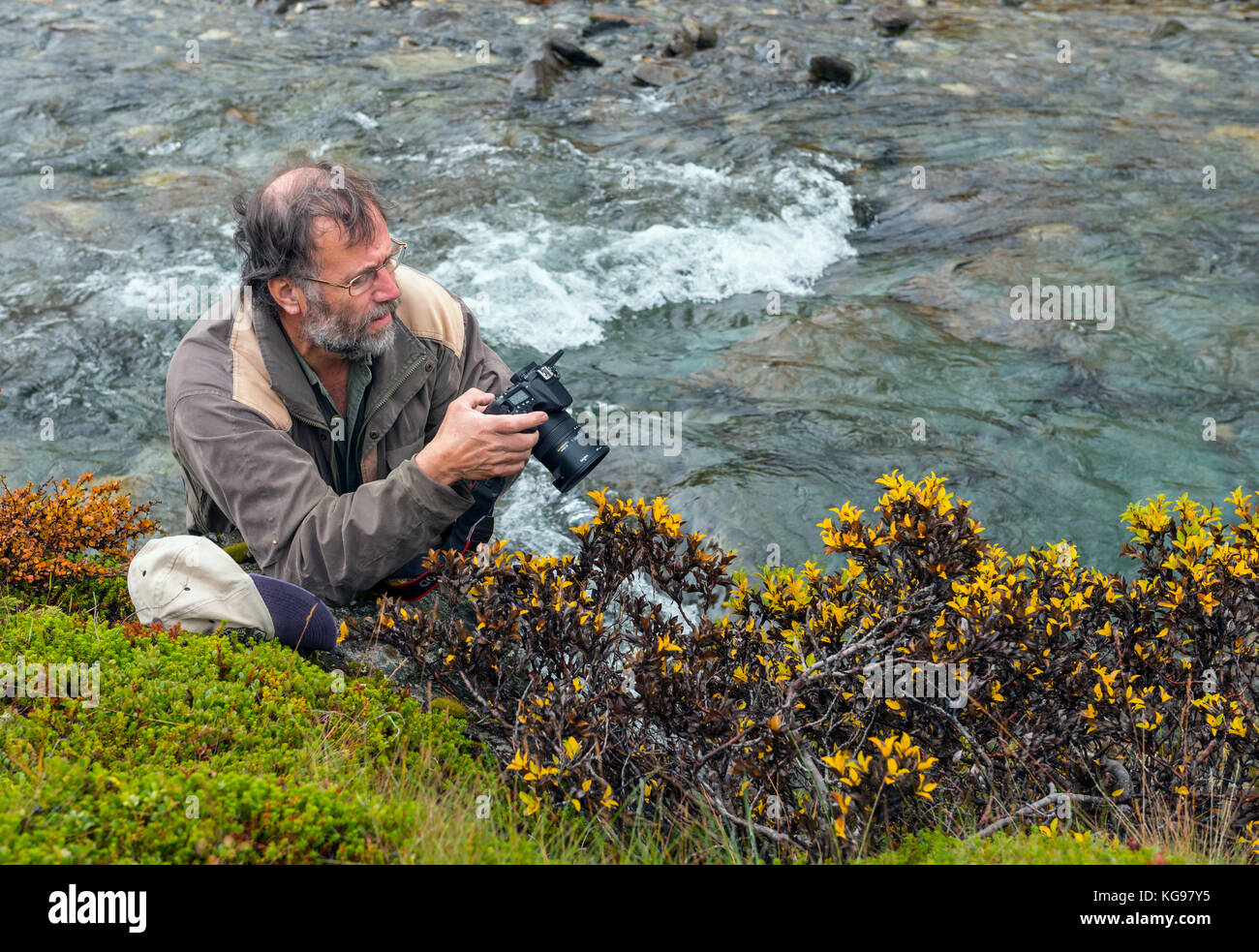 Nature photographer by a creek, Norway Stock Photo