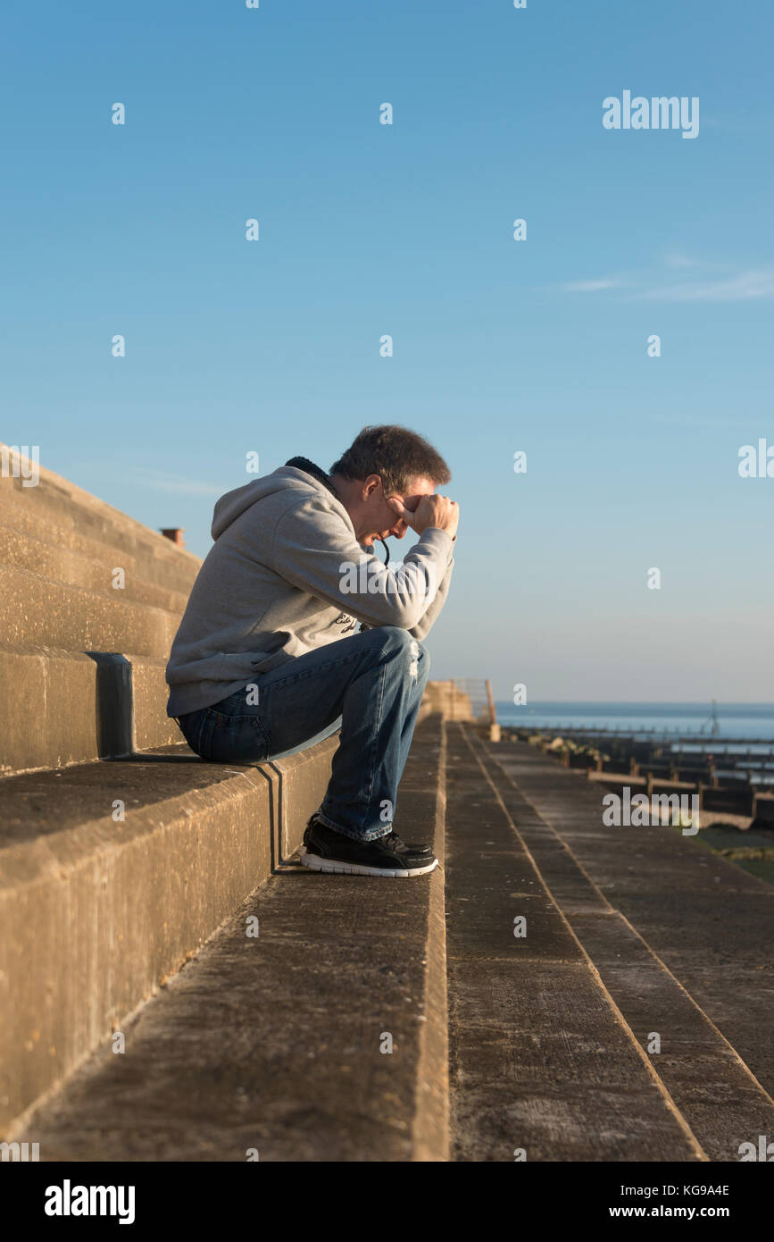 man with his head in his hands sitting on steps outside by the sea - Stock Image