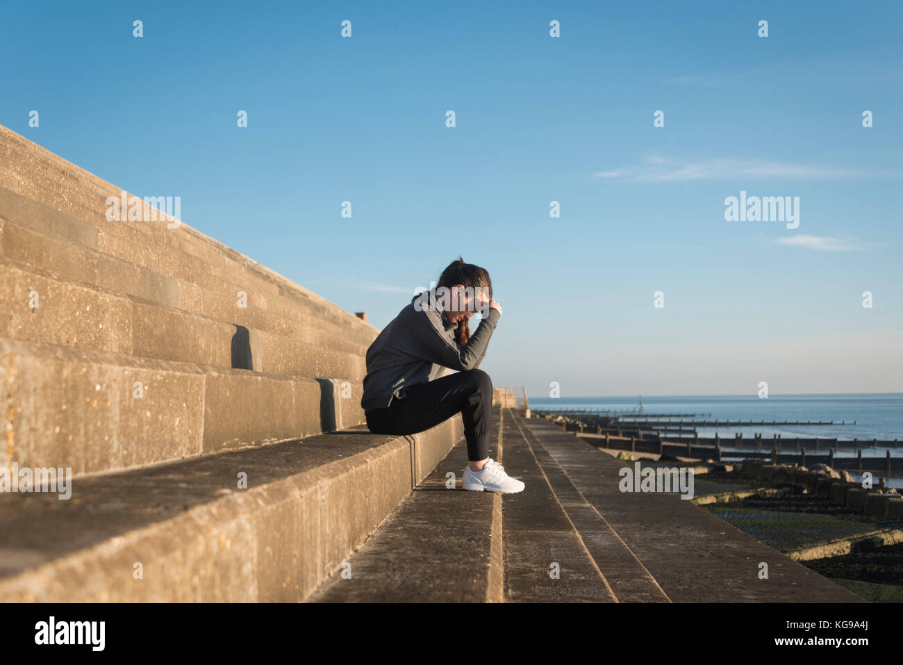woman sitting on steps outside by the sea with her head in her hands Stock Photo