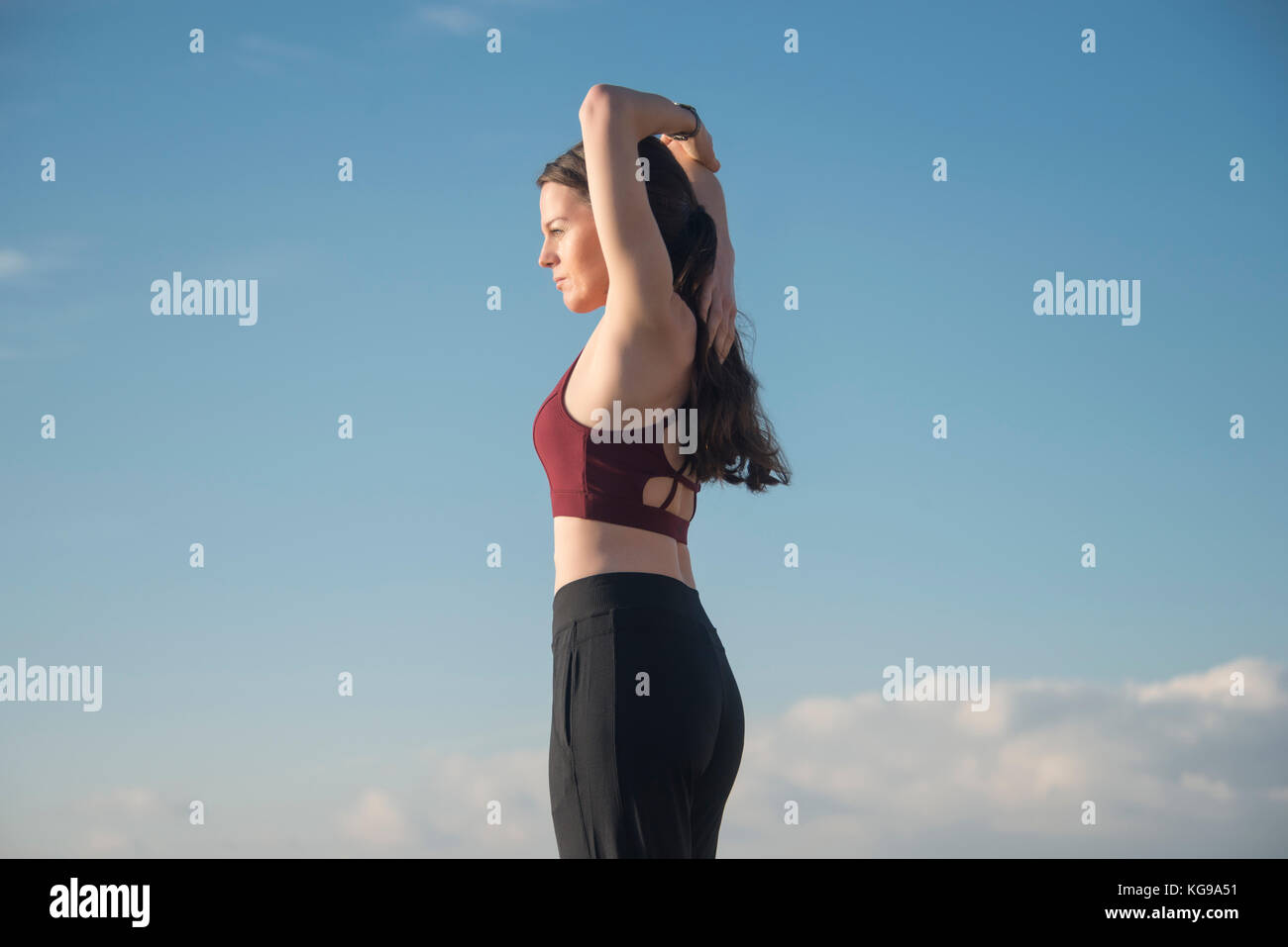 sporty woman wearing a sports bra doing an arm stretch outside keeping fit. - Stock Image