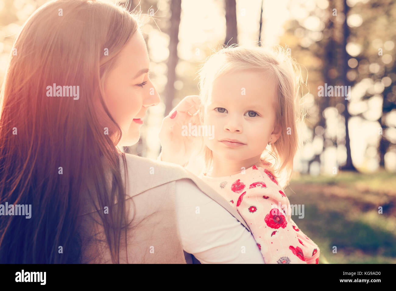 Young single mother holding cute toddler girl daughter in her arms and stroking her hair, girl power concept, daughter - Stock Image
