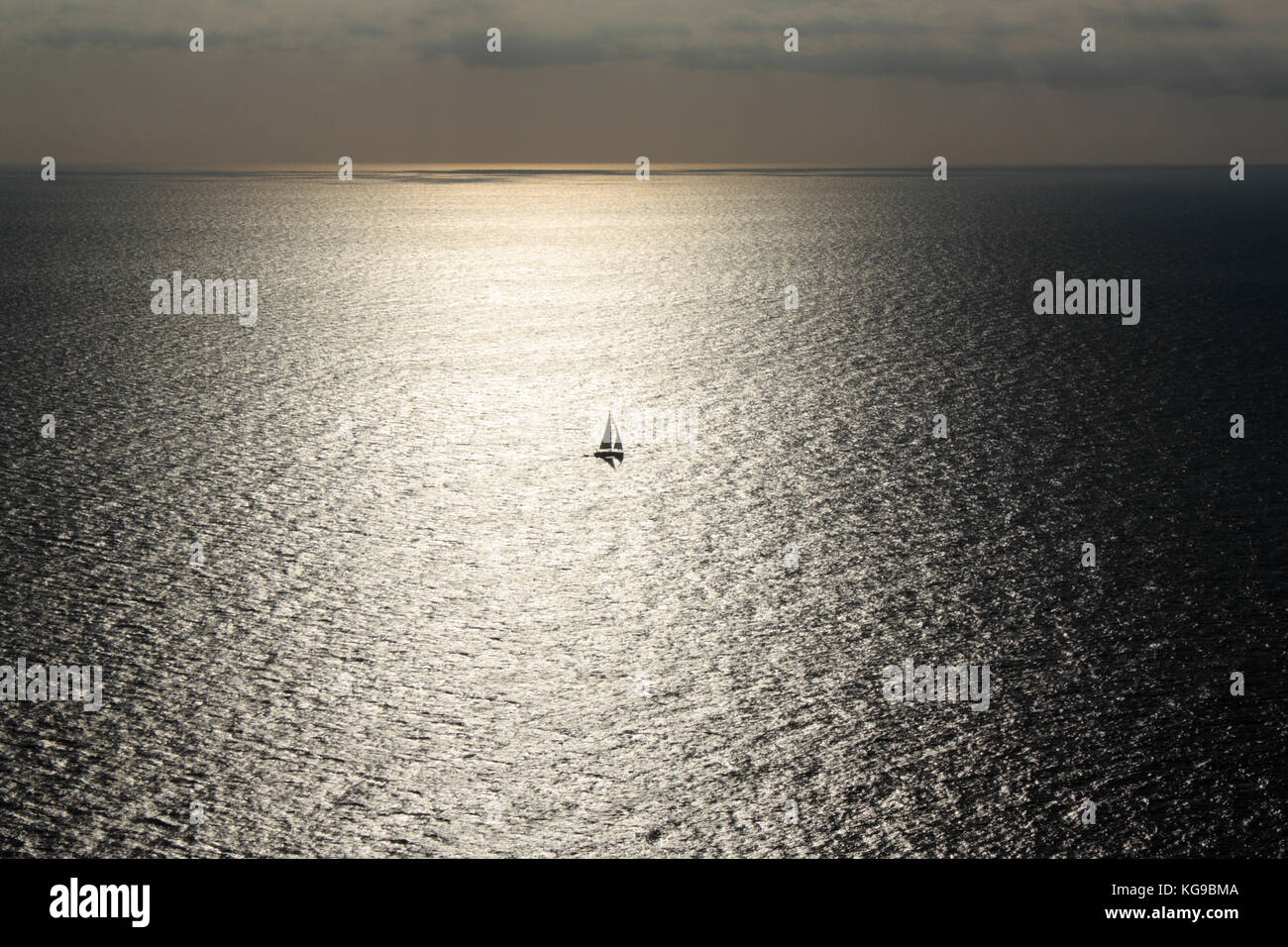Solitary sailing boat or yacht caught in the sun's reflections on a wide expanse of sea - Stock Image