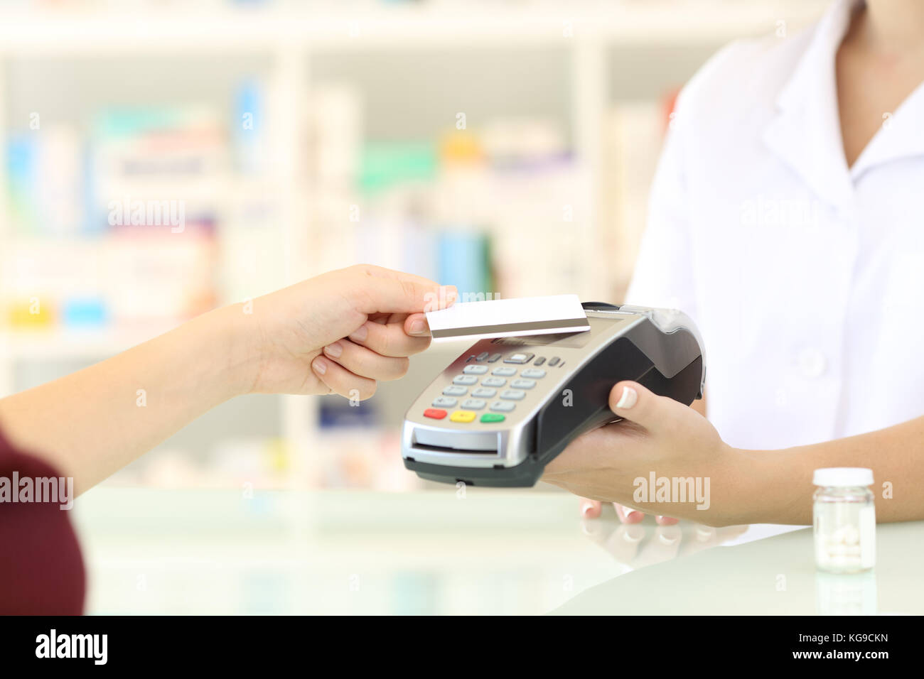 Close up of a customer hands paying with credit card reader in a pharmacy - Stock Image