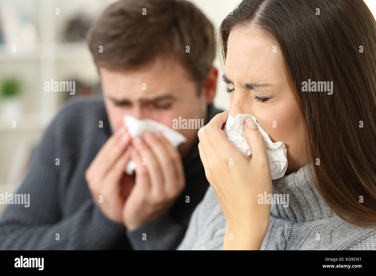 Ill couple wearing sweaters coughing together sitting on a sofa in the living room in a house interior - Stock Image