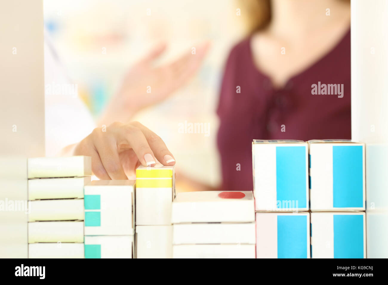 Close up of a pharmacist hands working attending to a customer in a pharmacy interior - Stock Image