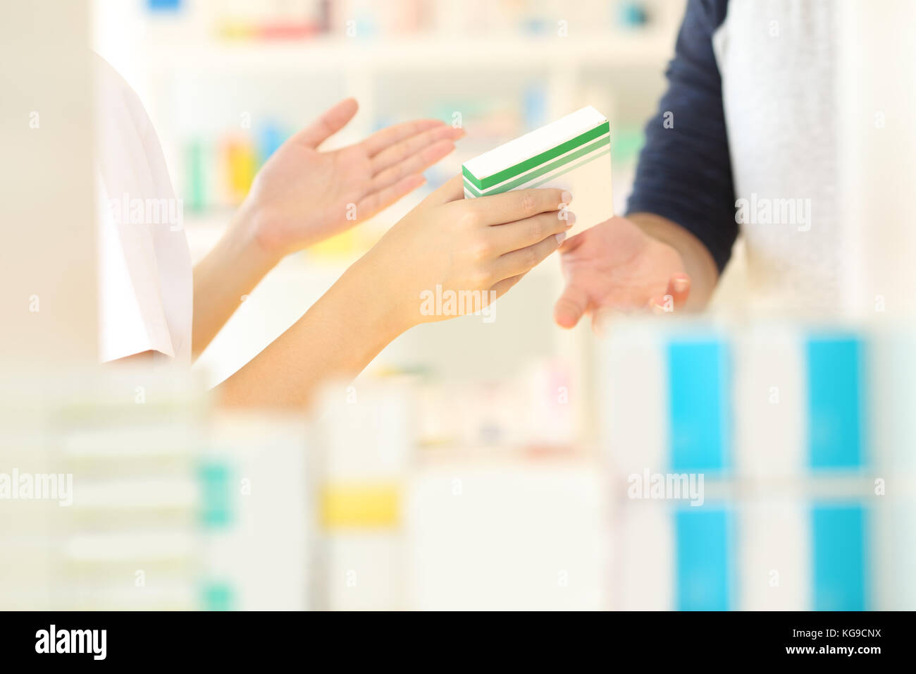 Close up of a pharmacist hands selling medicine to a customer in a pharmacy interior - Stock Image