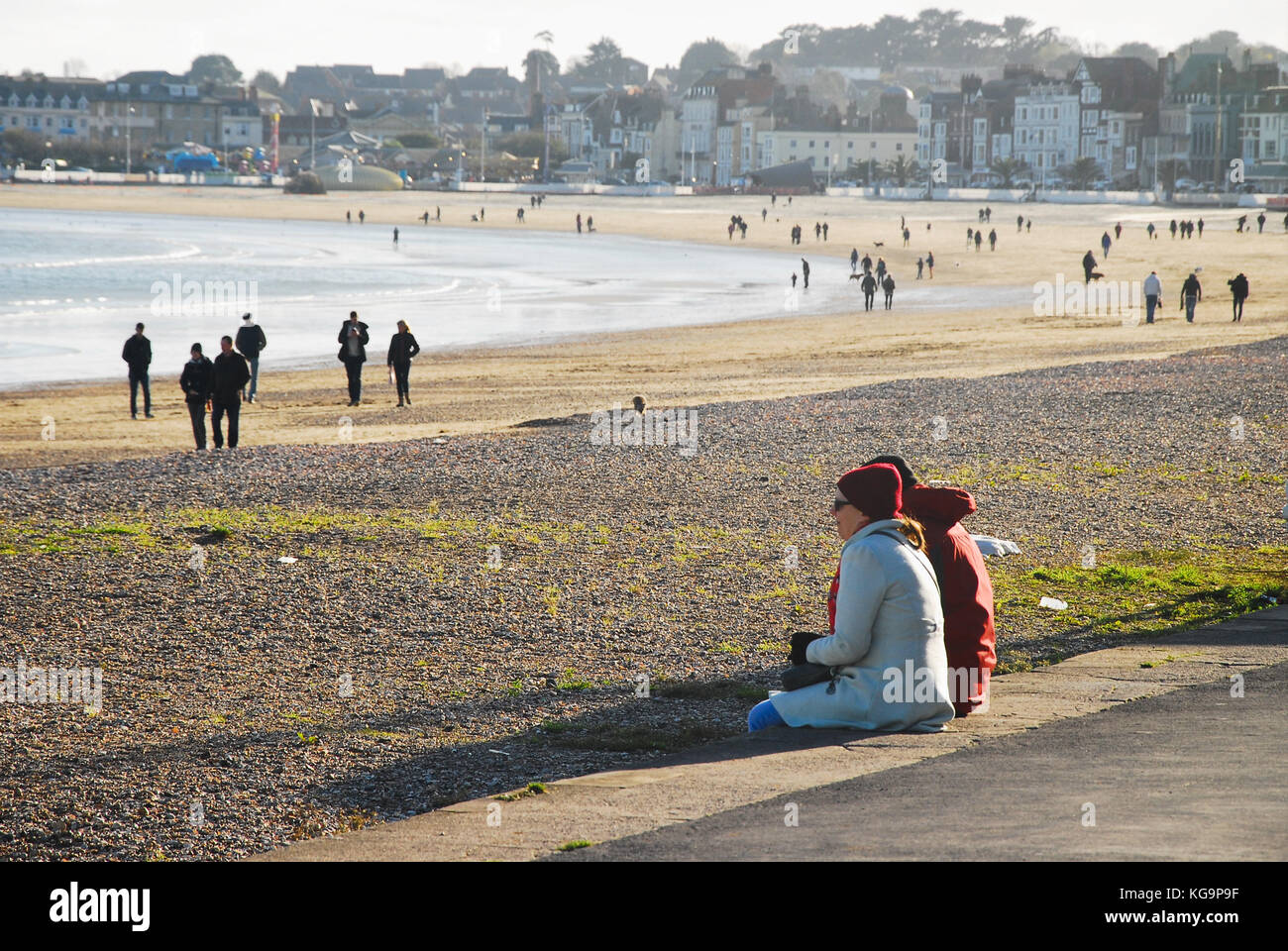 Weymouth, Dorset. 5th November 2017 - People wrap up warm and flock to Weymouth beach to enjoy the autumn sunshine. - Stock Image