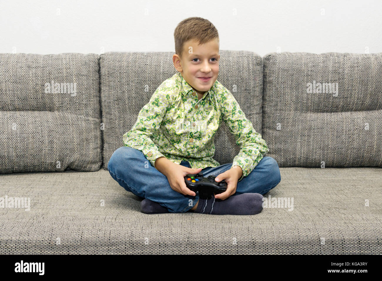 leisure, children, technology and people concept - smiling boy with joystick playing video game at home - Stock Image