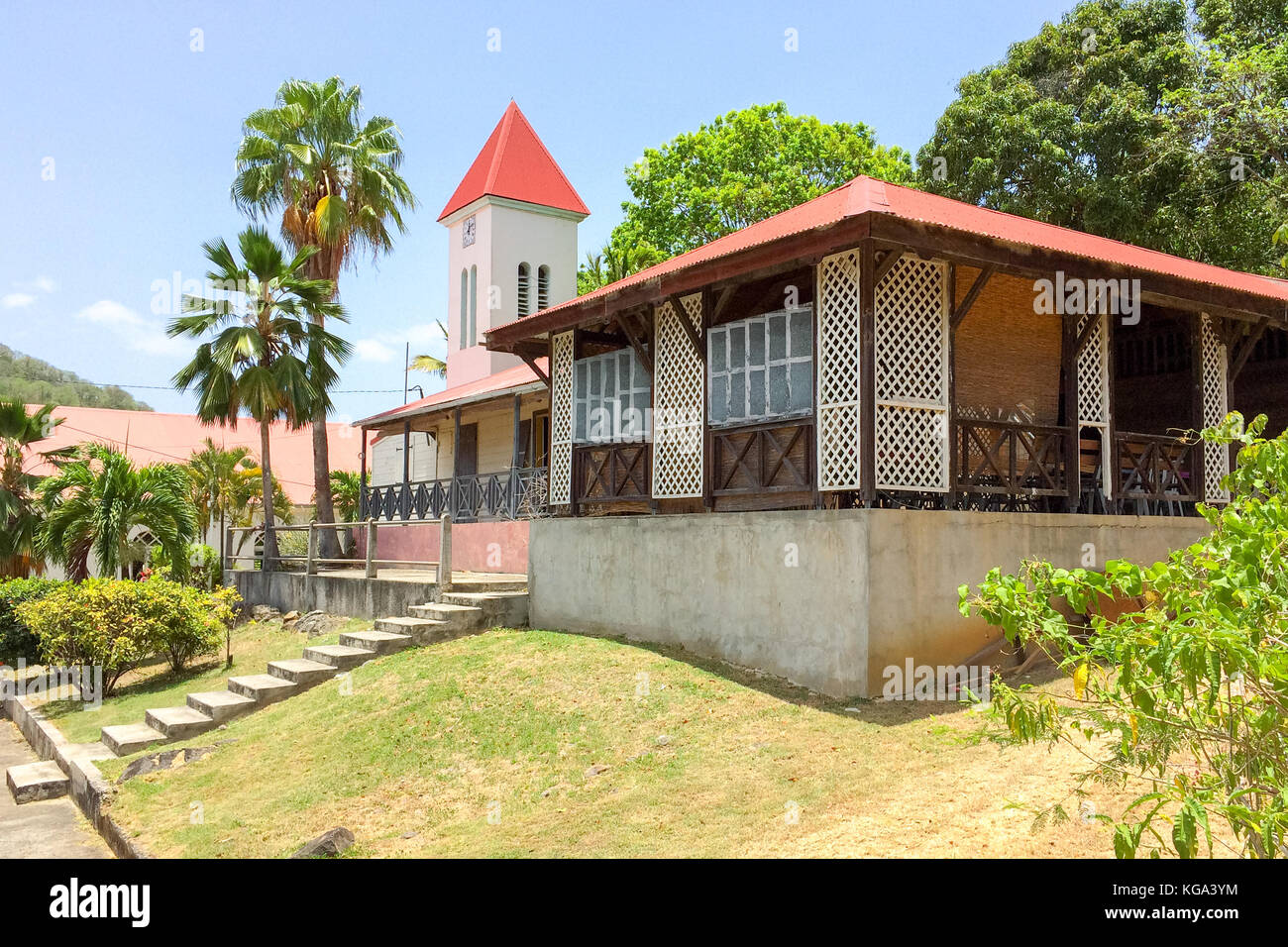 Side view of Deshaies church and surrounding buildings, used as set of English BBC tv movie Death in Paradise Stock Photo