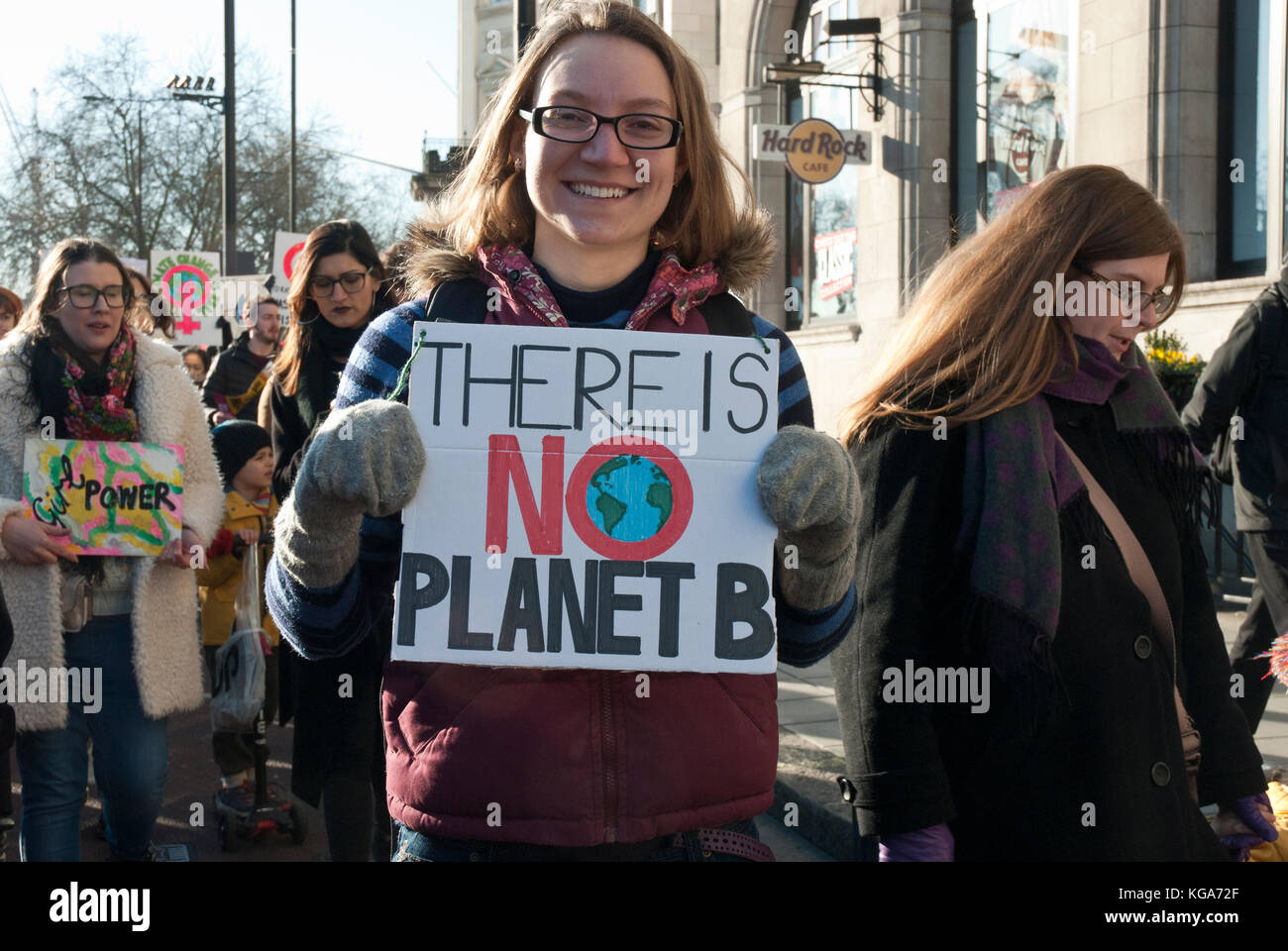 A young smiling activist holding a placard 'There is no Plant B' with a picture of planet Earth, as a comment - Stock Image