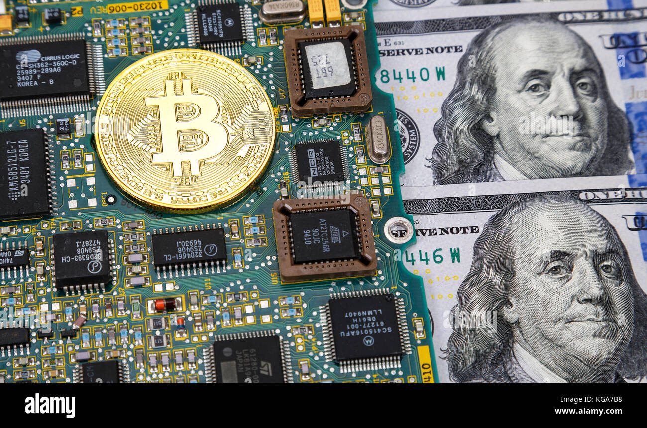 Moscow, Russia - November 5, 2017: Golden bitcoin lying over electronic computer component with american dollars - Stock Image