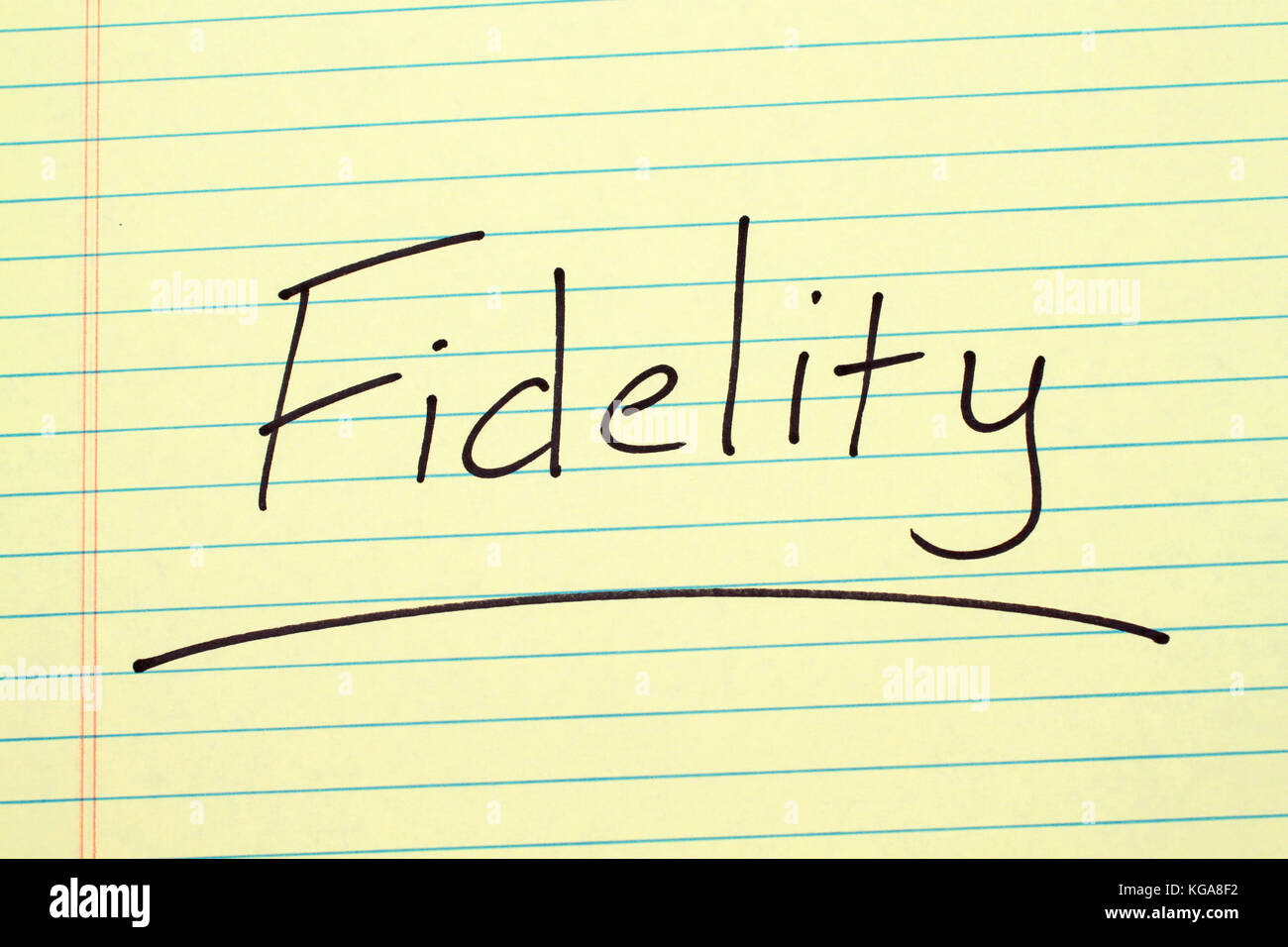 The word 'Fidelity' underlined on a yellow legal pad - Stock Image