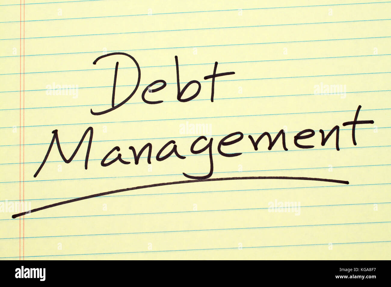 The word 'Debt Management' underlined on a yellow legal pad - Stock Image