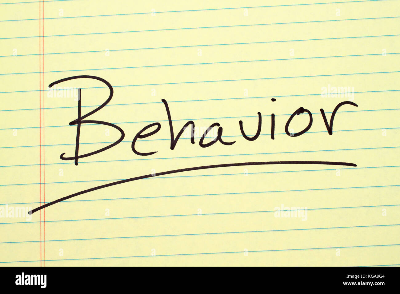The word 'Behavior' underlined on a yellow legal pad - Stock Image