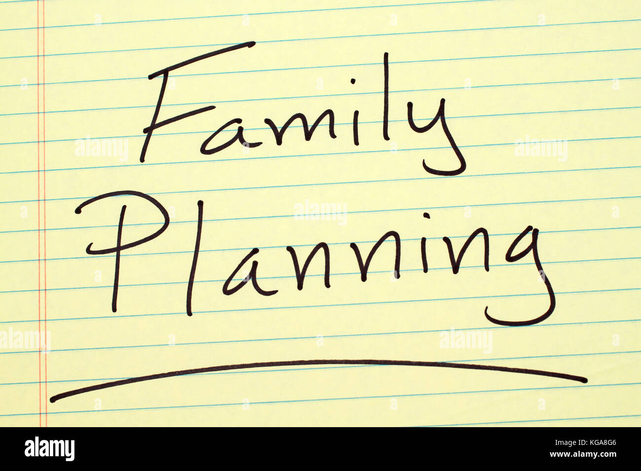 The word 'Family Planning' underlined on a yellow legal pad - Stock Image