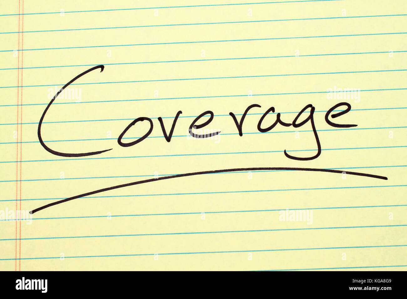 The word 'Coverage' underlined on a yellow legal pad - Stock Image