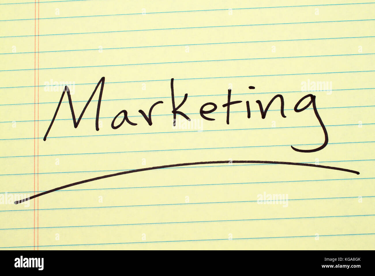 The word 'Marketing' underlined on a yellow legal pad - Stock Image