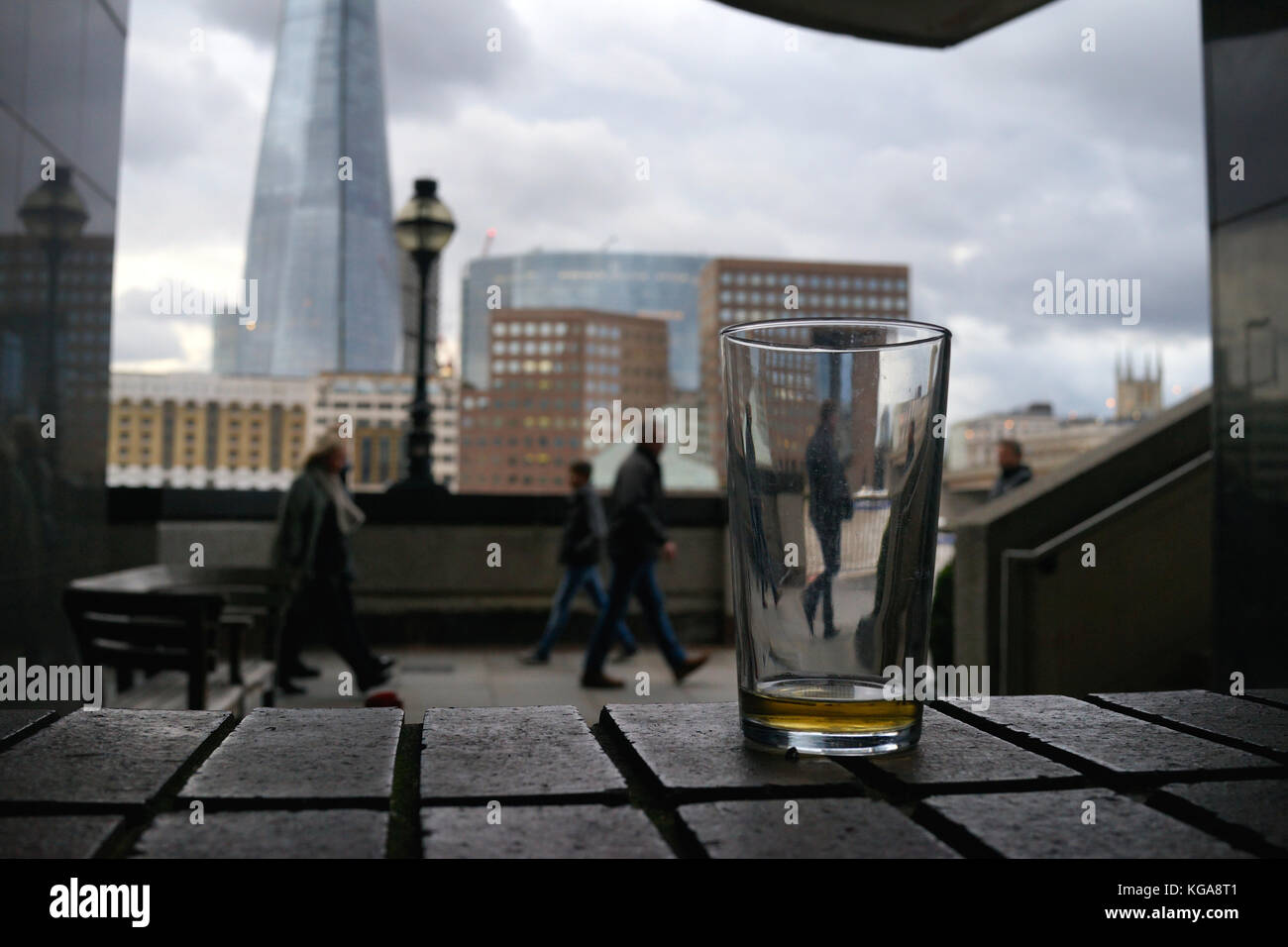 A pint glass by the side of the River Thames, London - Stock Image