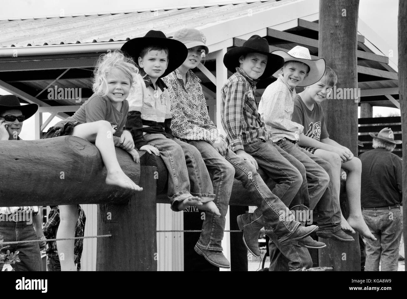 AUSTRALIAN COUNTRY KIDS SITTING ON FENCE. - Stock Image