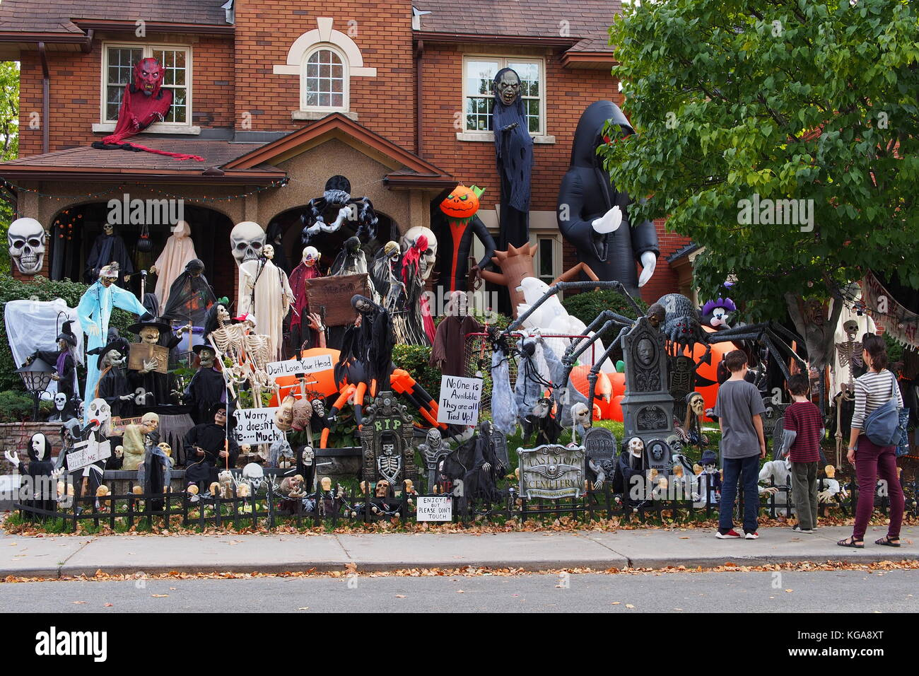 A family stops to view the elaborate Halloween garden decorations