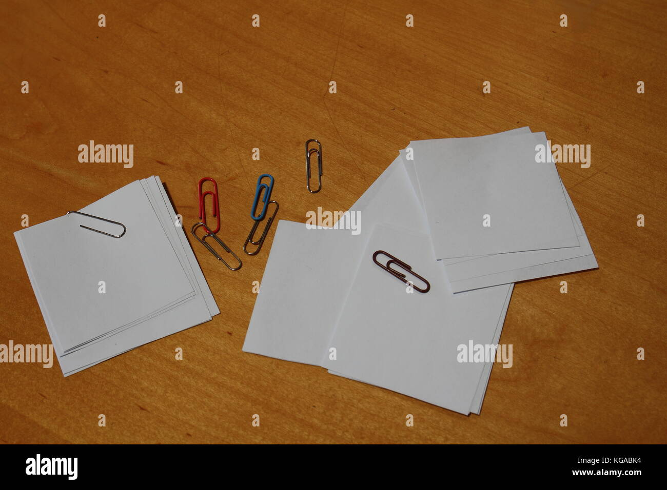 Paper clips and notes on a desk viewed from above with copy space - Stock Image