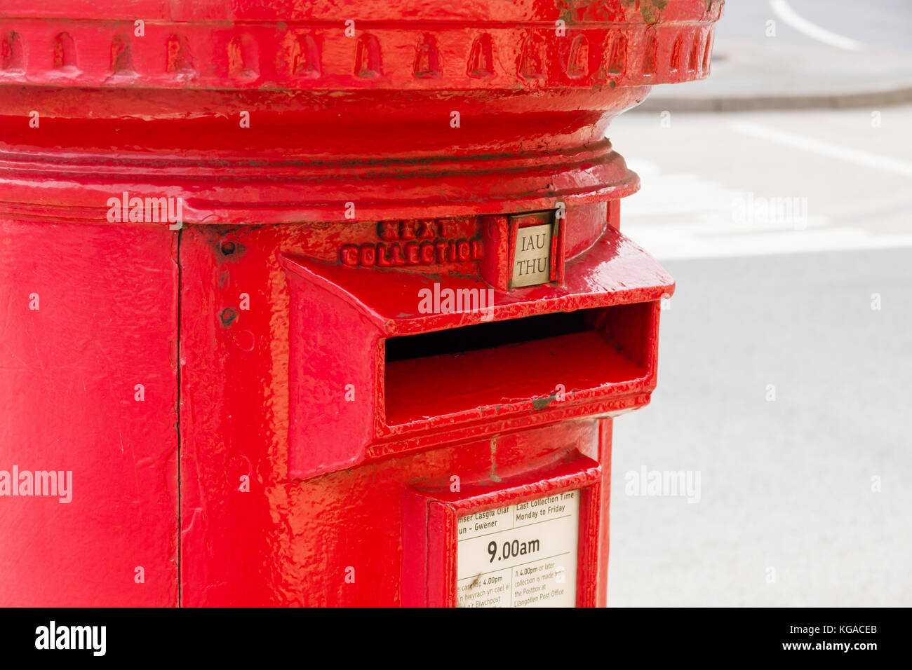 Classic style British red post box in Llangollen North Wales with bilingual Welsh and English collection times - Stock Image