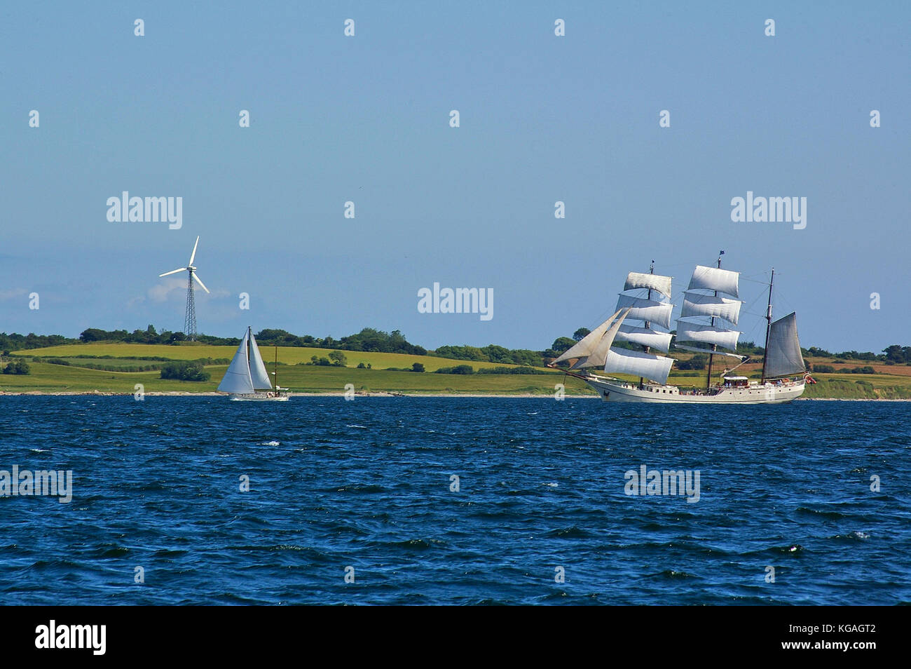 Traditional square-rigged tall ship and modern two-masted yacht at sea in front of a green seashore with fields - Stock Image